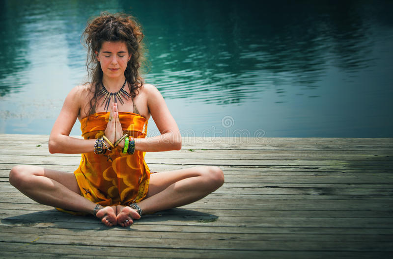 Woman in a meditative yoga position by lake stock photo