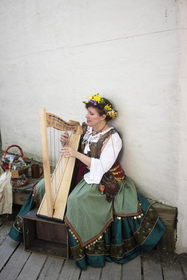 Woman in medival dress sitting on a bench playing a harp at Oklahoma Renaissance Festival Muskogee OK 5 13 2018 stock image
