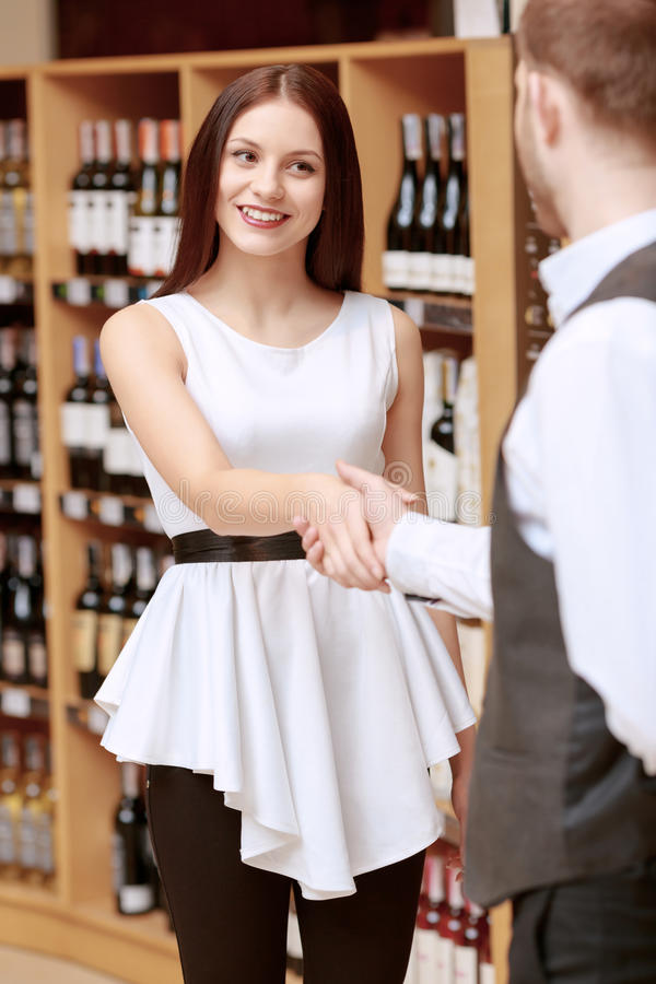 Woman meets sommelier in a liquor shop royalty free stock photography