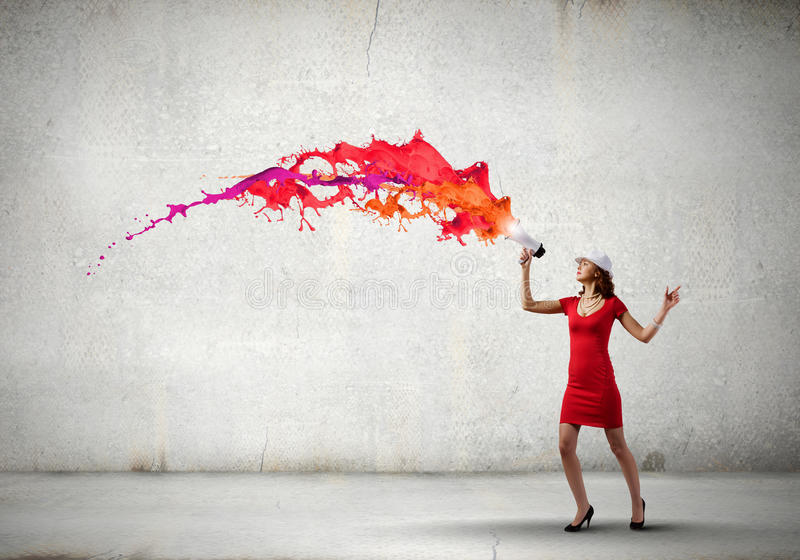Woman with megaphone. Pretty woman in red dress screaming in megaphone stock image