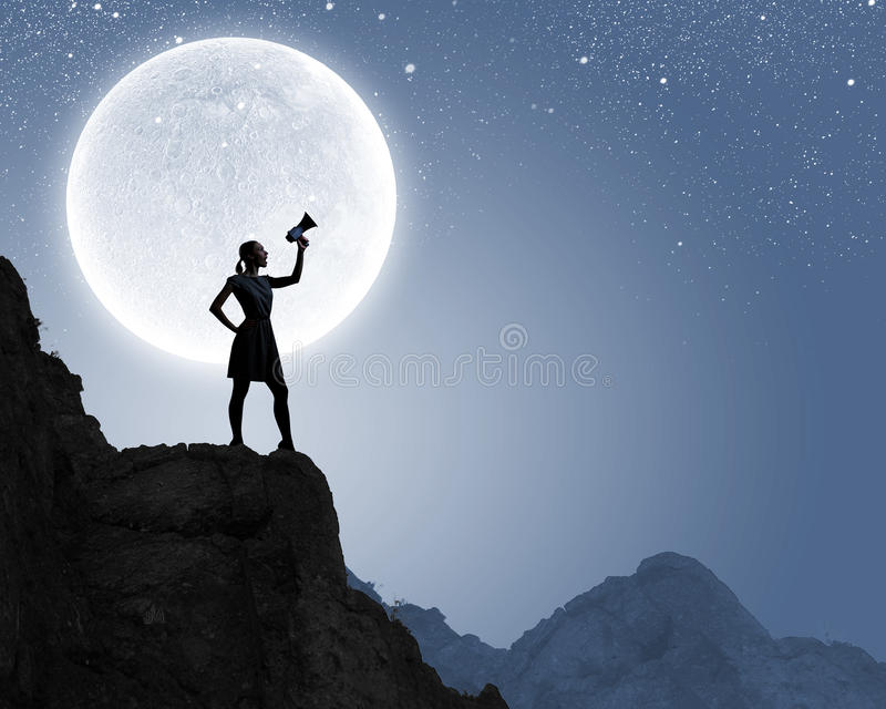 Woman with megaphone. Silhouette of woman on top of rock screaming in megaphone royalty free stock images