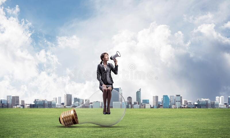 Woman with megaphone sitting on big light bulb royalty free stock photography