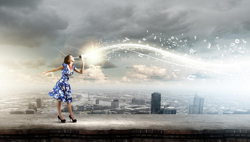 Woman with megaphone. Young woman in blue dress talking in megaphone stock photography