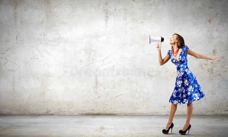 Woman with megaphone. Young woman in blue dress talking in megaphone royalty free stock photo