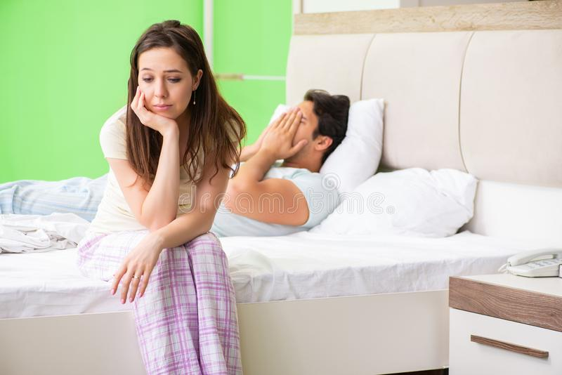 The woman and man in the bedroom after conflict. Woman and men in the bedroom after conflict stock photo