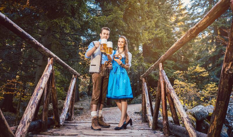 Woman and man with beer standing on bridge in Bavaria royalty free stock image