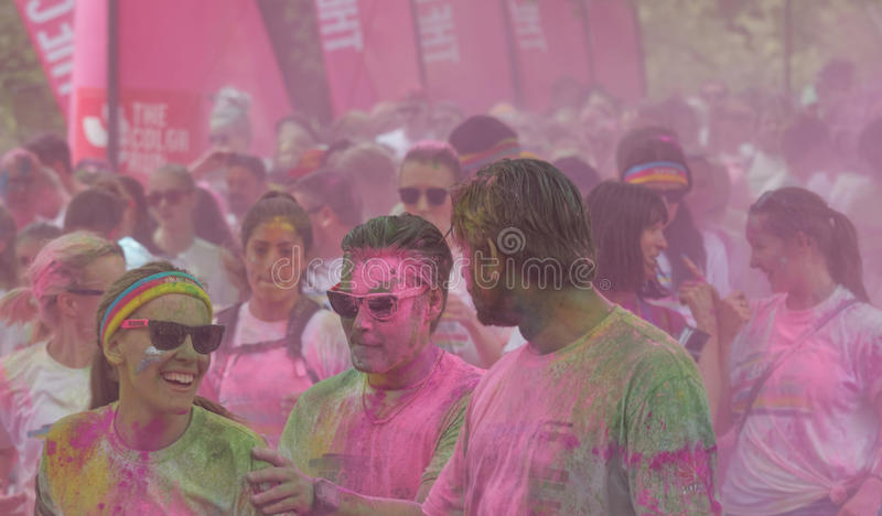 Woman and men covered with pink color powder walking royalty free stock photography