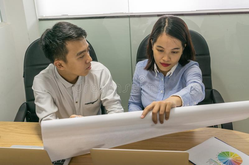 Woman and man discussing on project plan drawing paper royalty free stock image