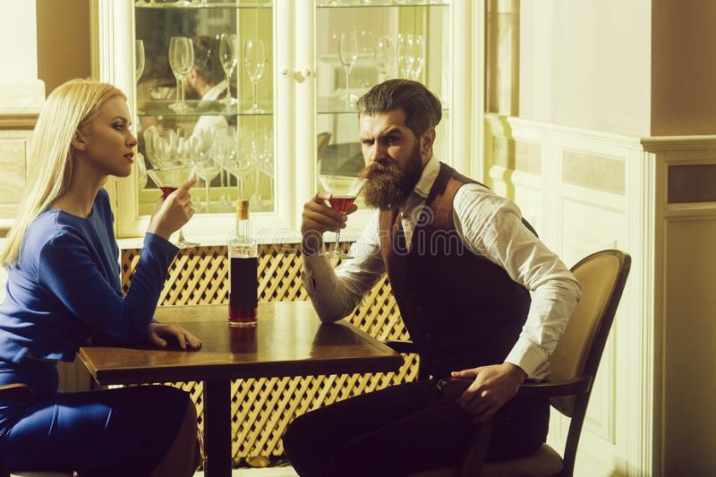 Woman and man drinking from martini glasses. Woman and men drinking from martini glasses. Girl and hipster sharing bottle of wine in restaurant. Couple in love royalty free stock photo