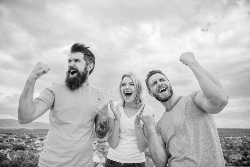 Woman and men look emotional successful celebrate victory sky background. Threesome winners happy with raised fists. We. Are winners. Celebrate success royalty free stock photo