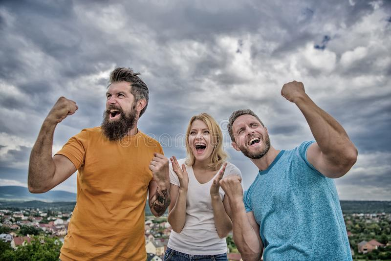 Woman and men look emotional successful celebrate victory sky background. Threesome winners happy with raised fists. We. Are winners. Celebrate success royalty free stock image