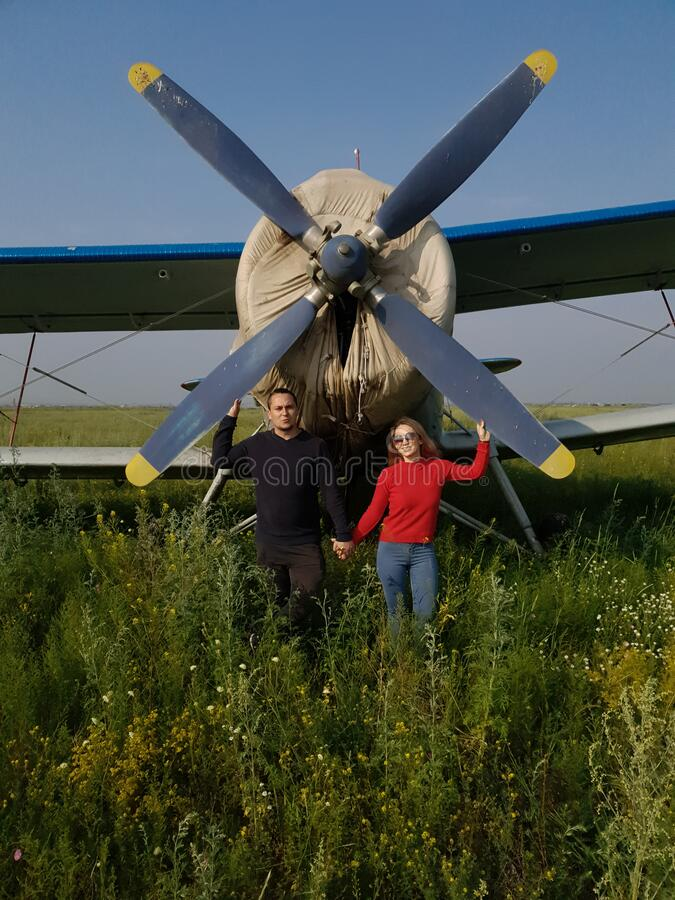 Woman and men portrait in front of an aircraft. Young couple with red jacket stand in front of older bomber aircraft. Woman and men portrait in front of an old stock photo