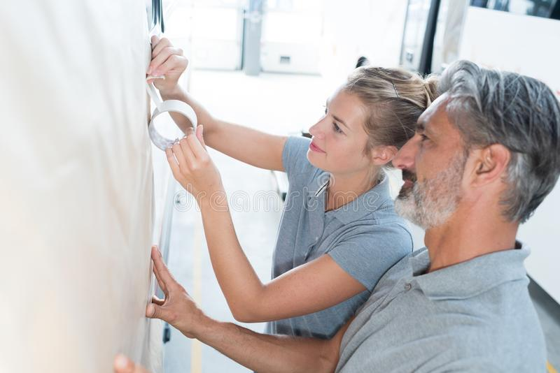 Woman and man using masking tape in workshop royalty free stock photography