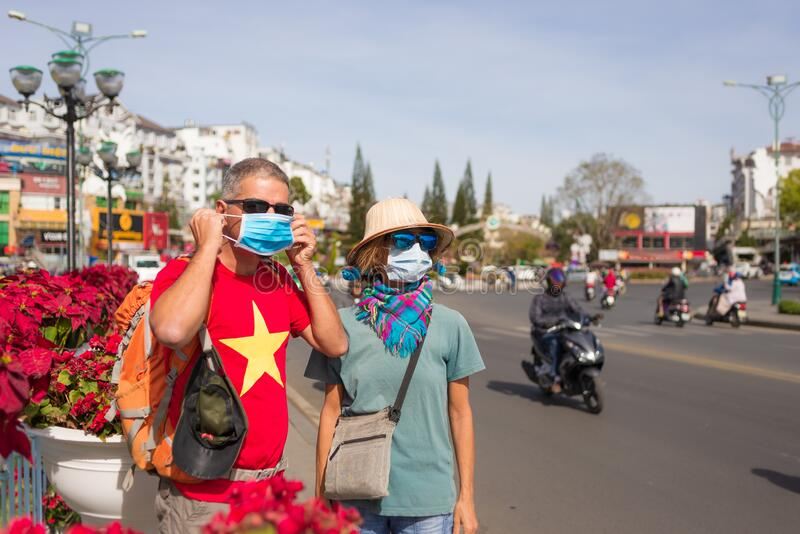 Woman and man wearing sanitary mask outdoors in Da Lat city centre Vietnam. Medical mask protection against risk of chinese flu stock photos