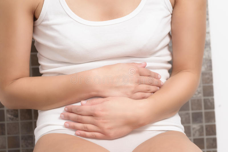 Woman with menstrual pains. Woman with her monthly menstrual pains clutching her stomach with her hands as she becomes stressed by the ongoing cramps, torso view royalty free stock photo