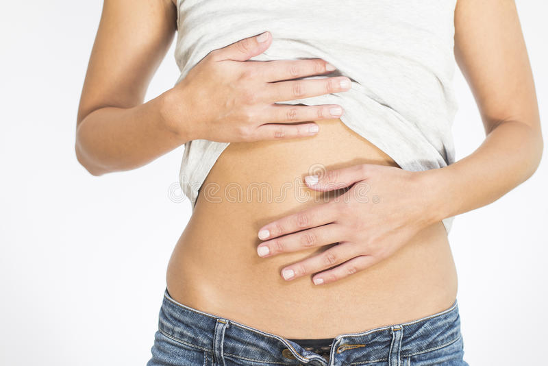 Woman with menstrual pains. Woman with her monthly menstrual pains clutching her stomach with her hands as she becomes stressed by the ongoing cramps, torso view stock photo