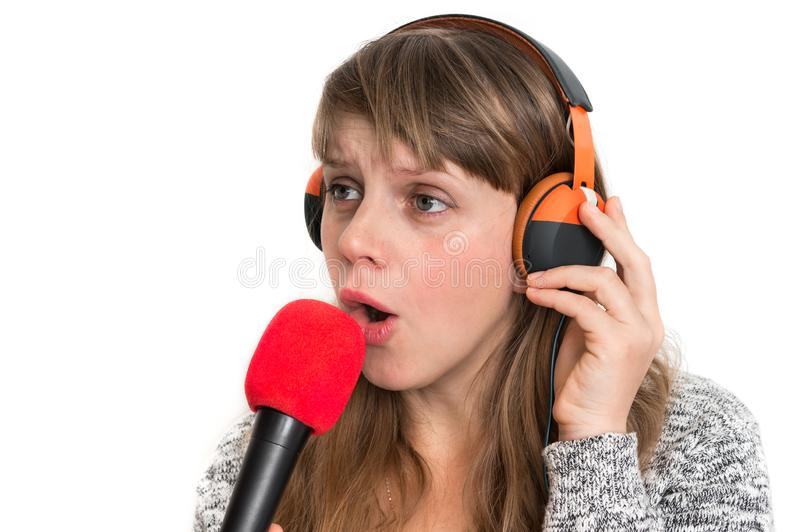 Woman with mic and headphones is recording her song. Pretty woman with mic and headphones is recording her song stock image