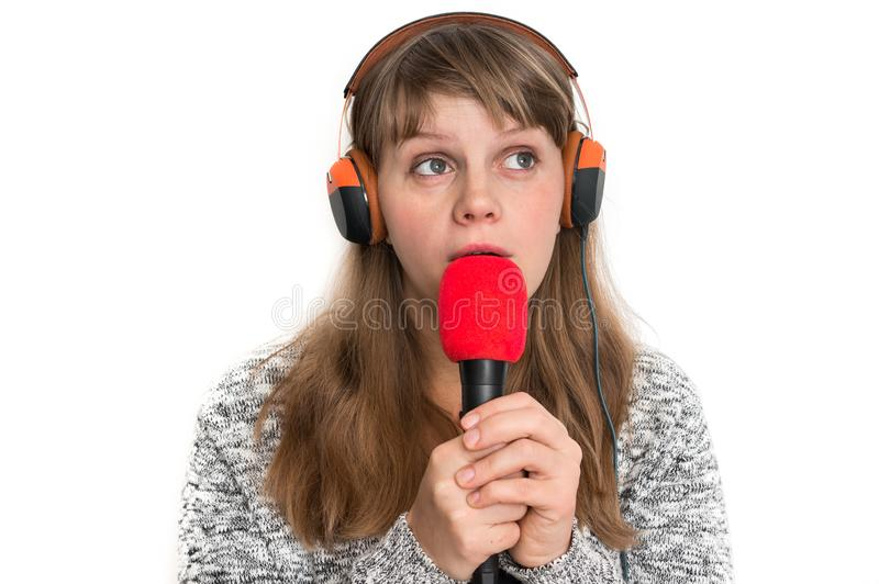 Woman with mic and headphones is recording her song. Pretty woman with mic and headphones is recording her song royalty free stock photo