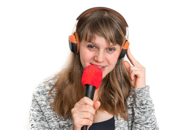 Woman with mic and headphones is recording her song. Pretty woman with mic and headphones is recording her song royalty free stock image