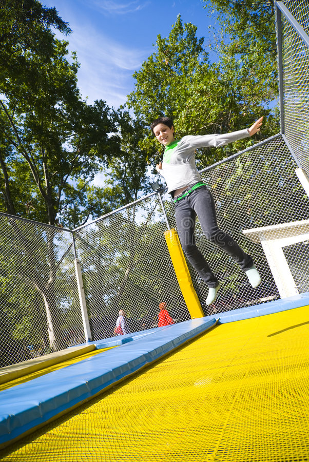 Woman in mid-air on trampoline stock photo