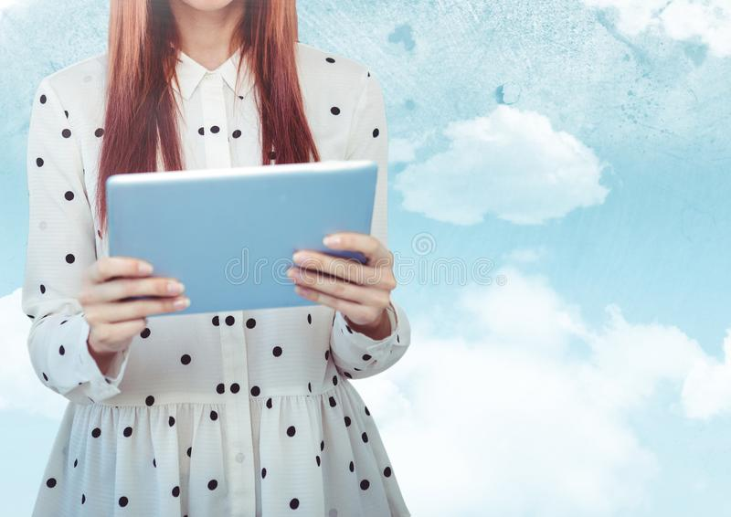 Woman mid section with polka dot top and tablet against sky with flare stock photography