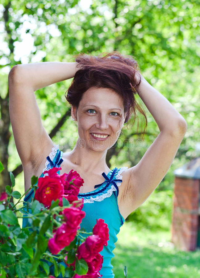 Woman of middle age near to a bush of roses. The woman of middle age near to a bush of roses royalty free stock photography