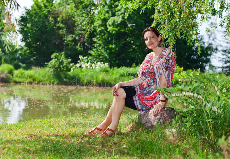 Woman of middle age in park. The woman of middle age has a rest in park stock photo