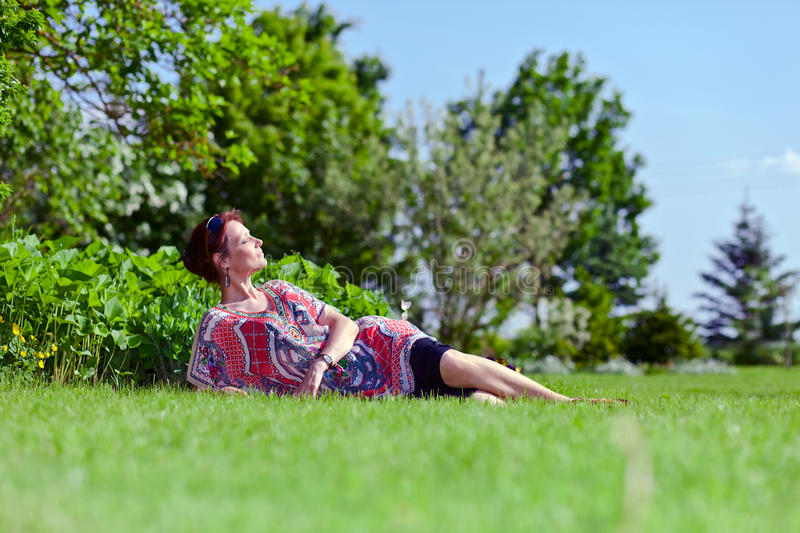 The woman of middle age in park. The woman of middle age has a rest on a grass in park royalty free stock photography
