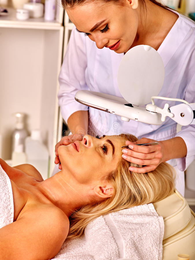 Woman middle-aged in spa salon. Tweezing eyebrow by beautician. stock image