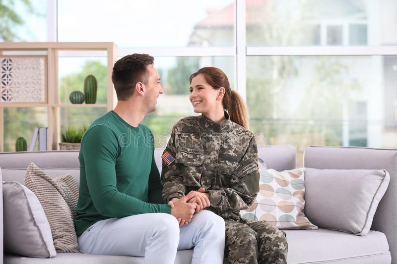 Woman in military uniform with her husband on sofa stock photo