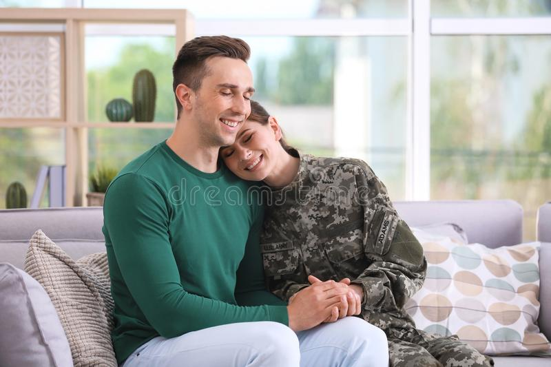 Woman in military uniform with her husband on sofa stock image