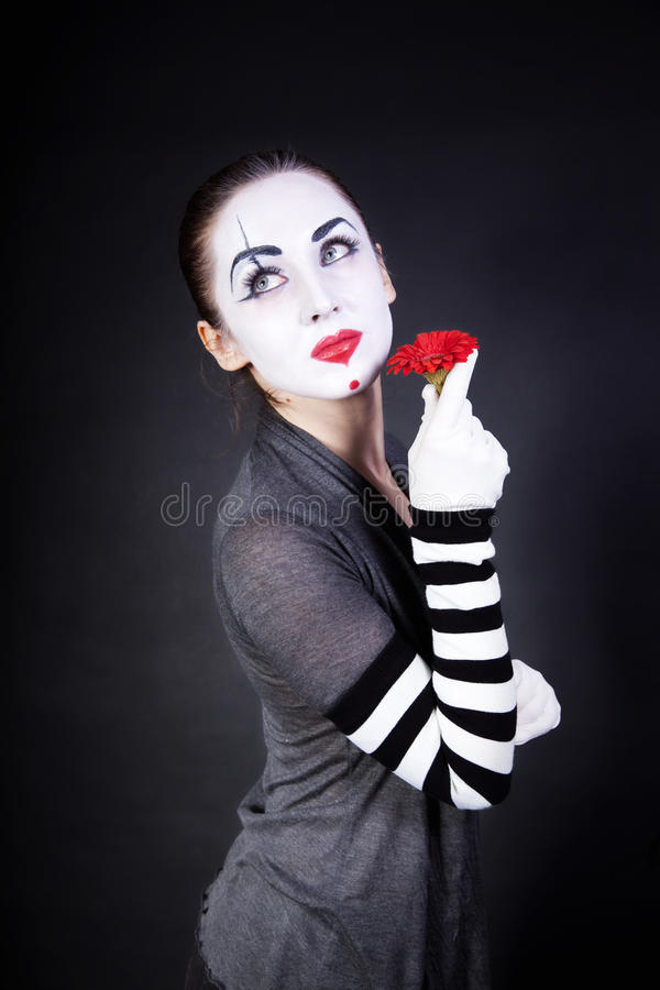 Woman mime with theatrical makeup. And red flower in hands on black background stock image