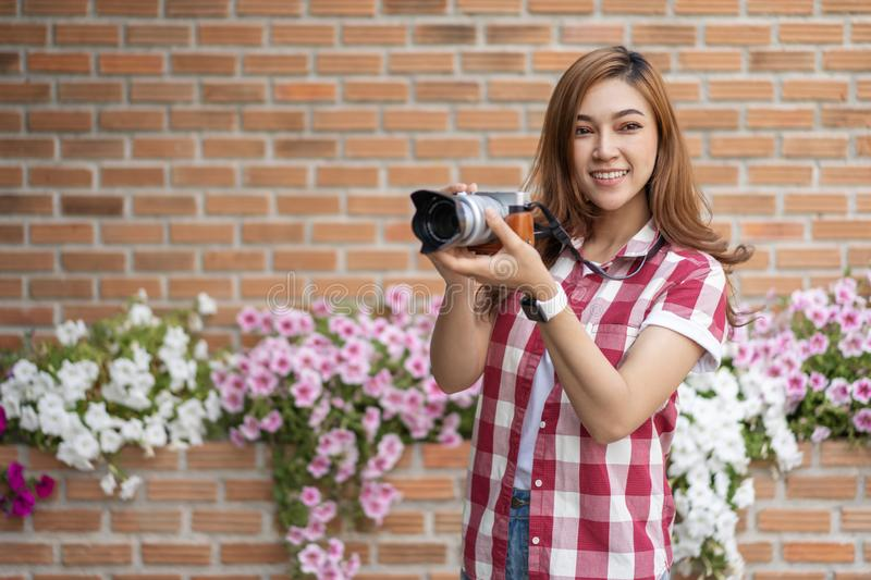 Woman with mirrorless camera. On brick wall background stock photo