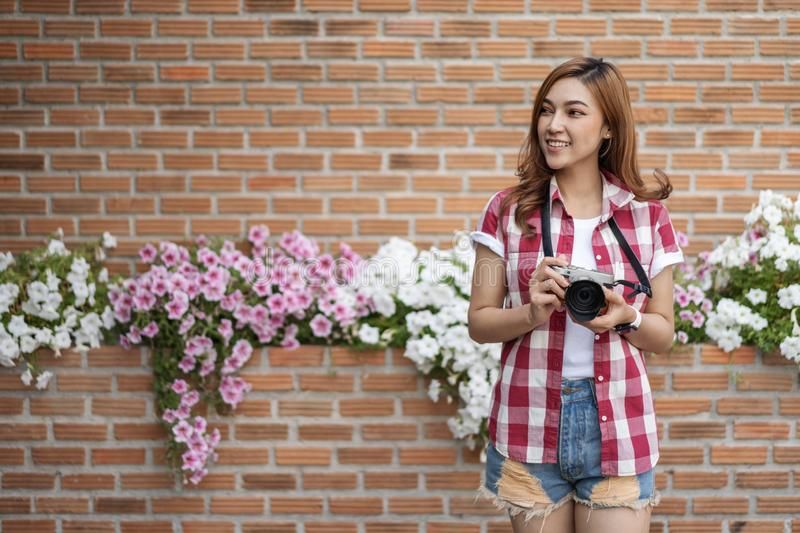 Woman with mirrorless camera. On brick wall background royalty free stock photos