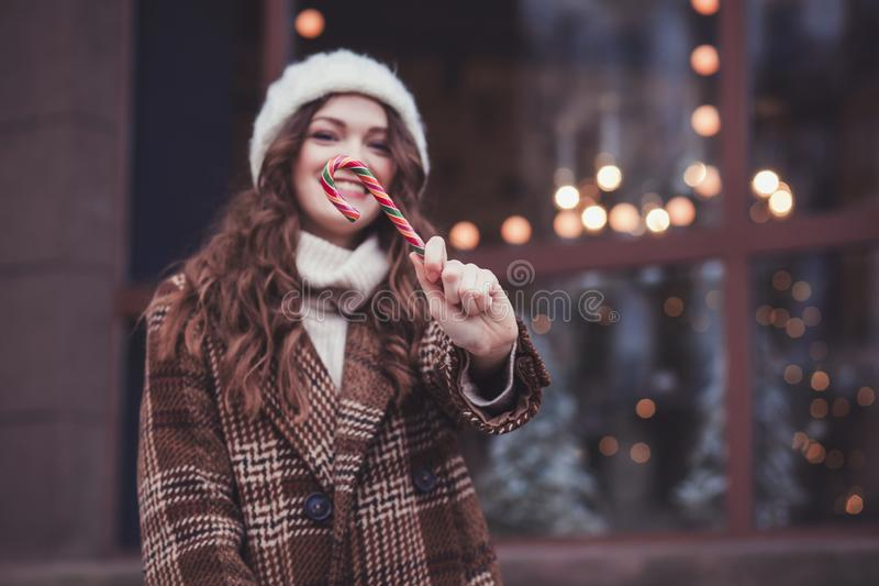 Woman in mittens holding an lollipop stock image