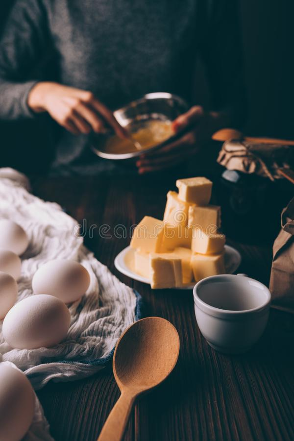 Woman mixing sugar and yolks. Process of cooking dough for pie. Woman mixing sugar and yolks in metal bowl next to diced butter and eggs on brown wooden table stock images