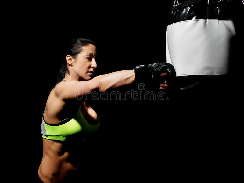 Woman in mma gloves fighting with boxing bag royalty free stock photography