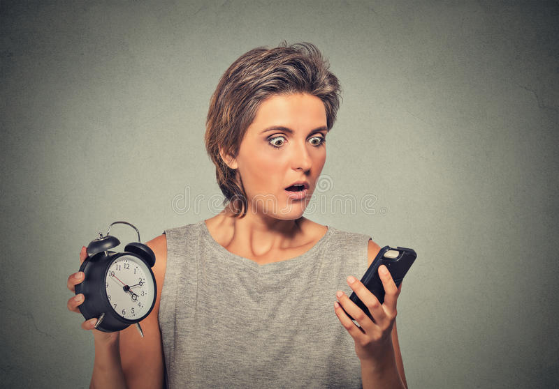 Woman with mobile phone and alarm clock stressed running late royalty free stock images