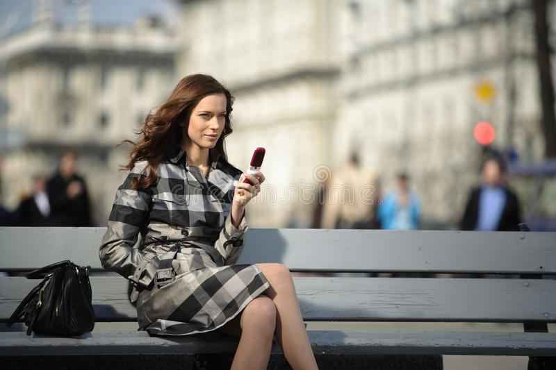 Woman with mobile phone at city background royalty free stock photo