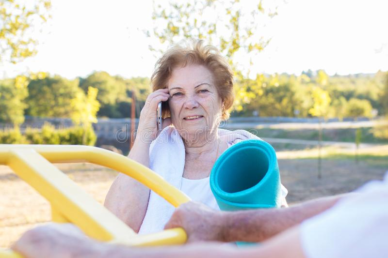 Senior woman with mobile phone doing sports royalty free stock photography