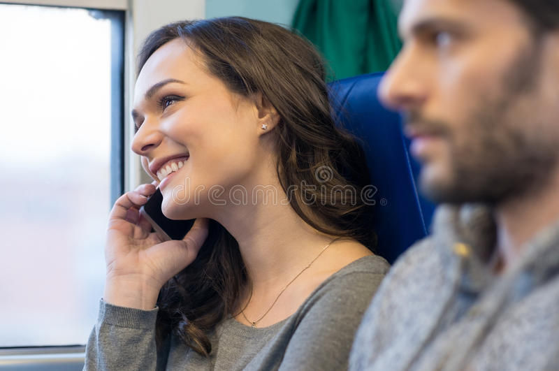 Woman on mobile phone. Portrait of a happy young women talking on telephone whiel travelling on train. She is looking away and out of the window. She is smiling royalty free stock images