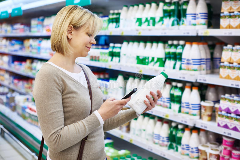 Woman with mobile phone shopping milk. In grocery store