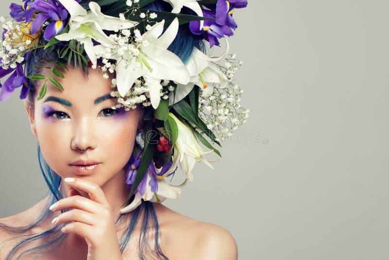 Woman modèle asiatique parfait avec les fleurs vives et le maquillage de mode photographie stock libre de droits