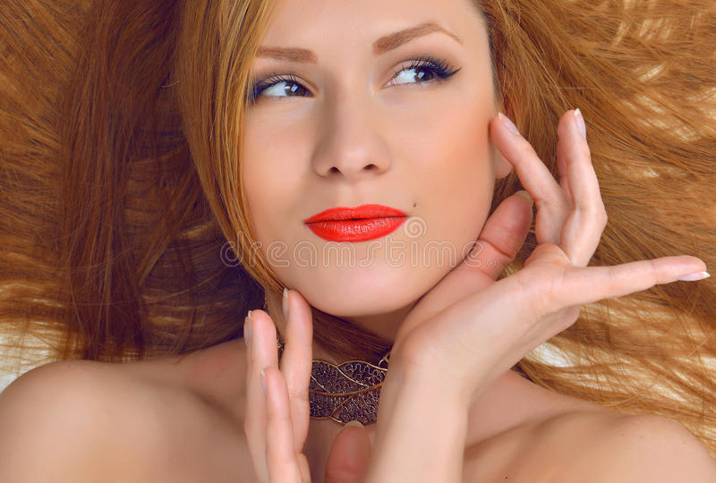 Woman model with glamour red lips make makeup lying on a floor w royalty free stock images