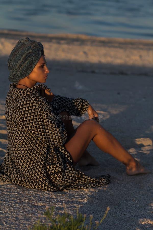 Woman in turban and coat sitting on sandy sea beach stock photos