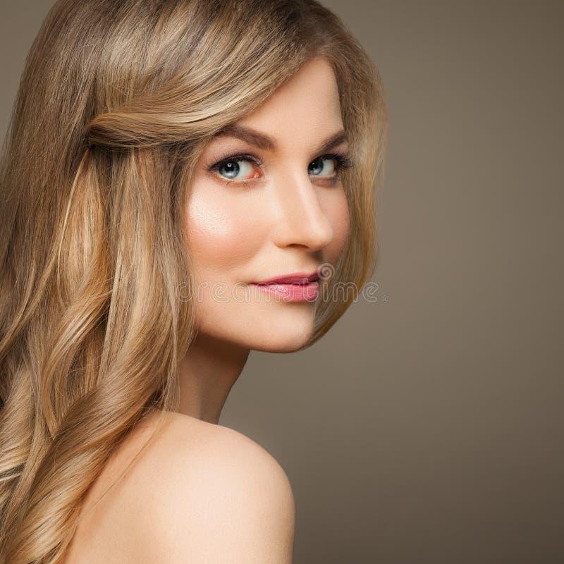 Woman modelo lindo con el pelo rubio en fondo beige foto de archivo libre de regalías