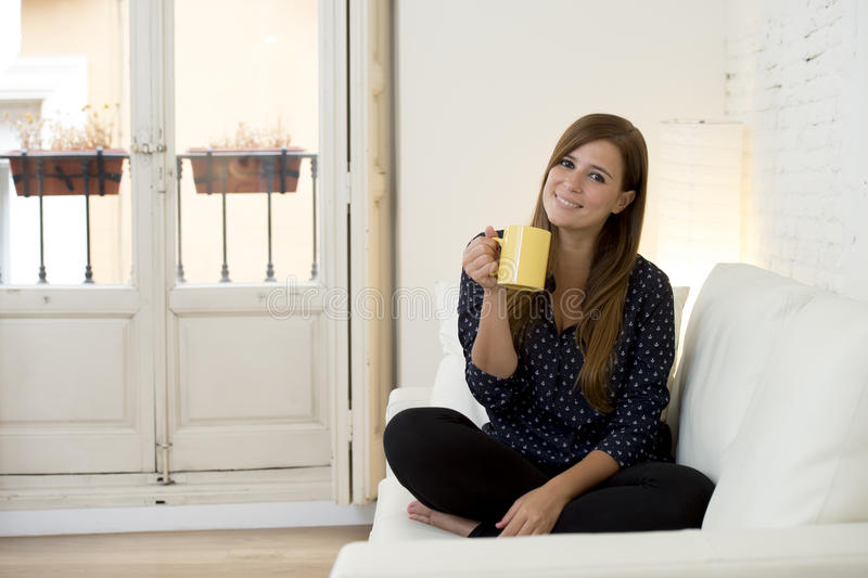 Woman at modern apartment living room home couch enjoying coffee tea cup. Young attractive woman sitting comfortably at modern apartment living room home couch stock photography