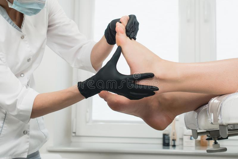 Woman in a modern beauty salon. pedicure procedure. The pedicure master in black gloves makes a preliminary review of the client`s legs to identify problems stock photo