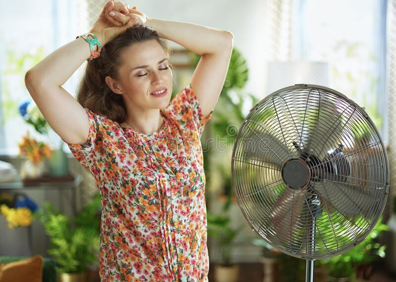 Woman at modern home in sunny hot summer day fanning herself royalty free stock images