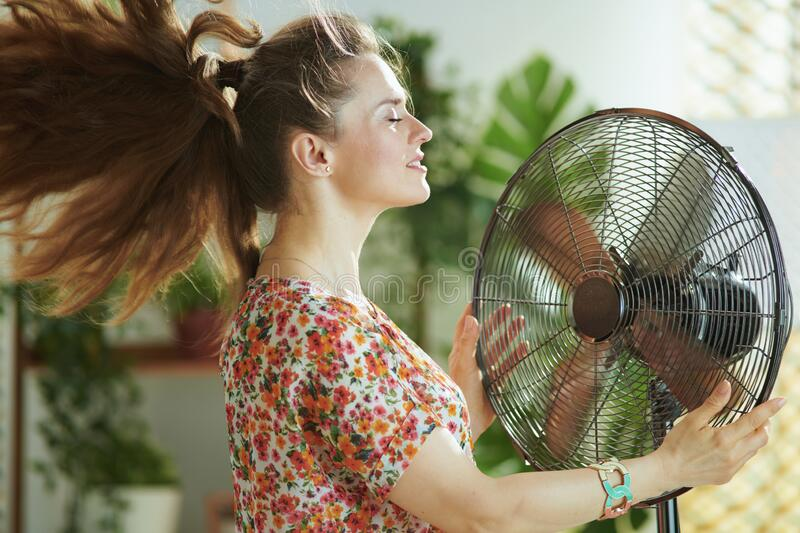 Woman in modern house in sunny hot summer day fanning herself stock image